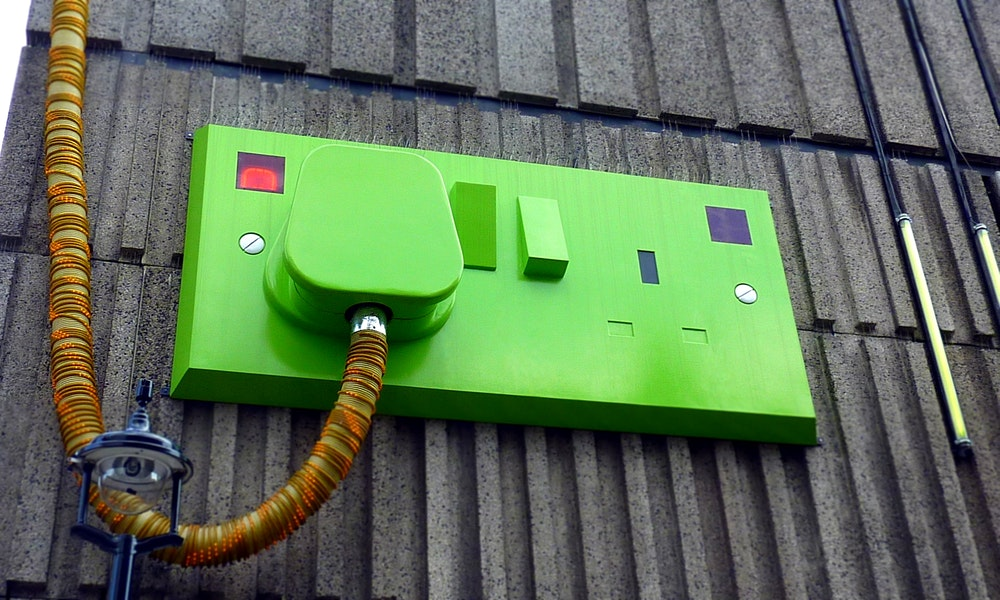 green-rectangular-corded-machine-on-grey-wall-during-daytime